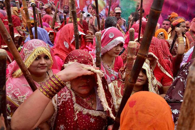 Devotees celebrate Latthmaar Holi at Dauji Temple
